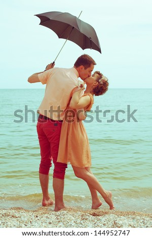 Summer vacation concept. Couple standing on beach near water, holding black umbrella and kissing each other. Hipster style. Happy together. Outdoor shot