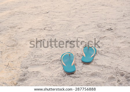 Summer vacation concept. Flip flops on a sandy ocean beach in vintage tone color style, selective focus (detailed close-up shot) - stock photo