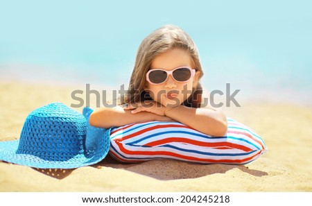 Summer vacation concept, joyful child in sunglasses and hat having fun lying on the sand coast sea - stock photo