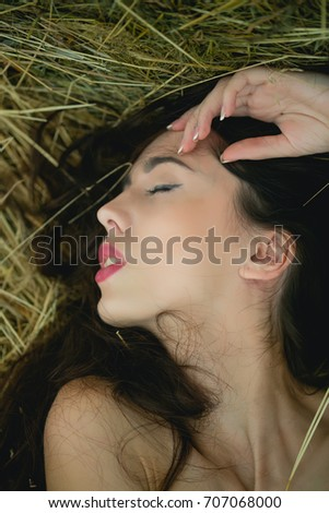 Summer vacation concept. Leisure and relaxing on nature. Girl lying in hay. Woman with closed eyes and brunette hair. Model with bare shoulders.