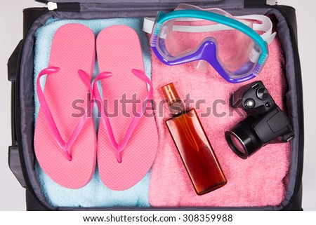 summer vacation concept - packed suitcase full of colorful vacation items - stock photo