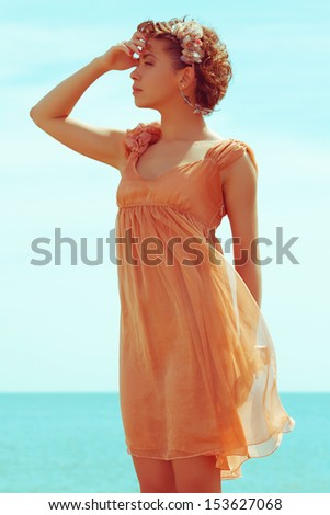 Summer vacation concept: portrait of a beautiful model with great tan wearing trendy dress, posing and standing at the seaside. Girl waiting for her boyfriend. Hipster style. Outdoor shot