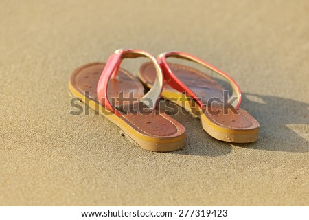 Summer vacation concept. Sandals on a sandy ocean beach