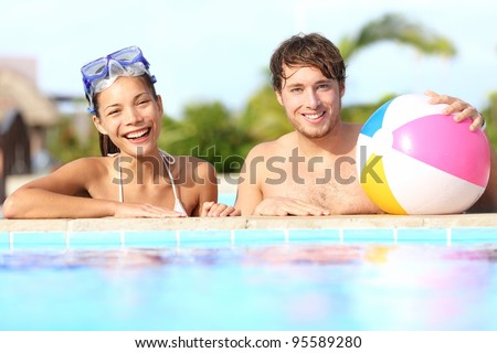 Summer vacation couple having fun in pool on sunny day in tropical resort - stock photo