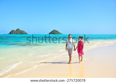 Summer vacation couple walking on beach landscape. Young adults relaxing together enjoying their holidays by pristine turquoise water on Lanikai beach, Oahu, Hawaii, USA with Mokulua Islands. - stock photo