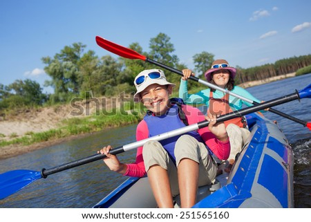 Summer vacation - Cute girl with mother kayaking on river. - stock photo