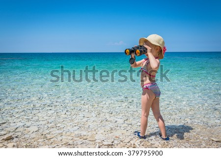 Summer vacation. Cute little girl in a bathing suit sunning on the beach. 2