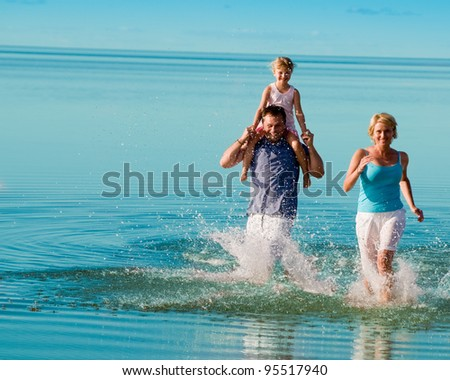 Summer vacation - family playing on the beach (space for text) - stock photo