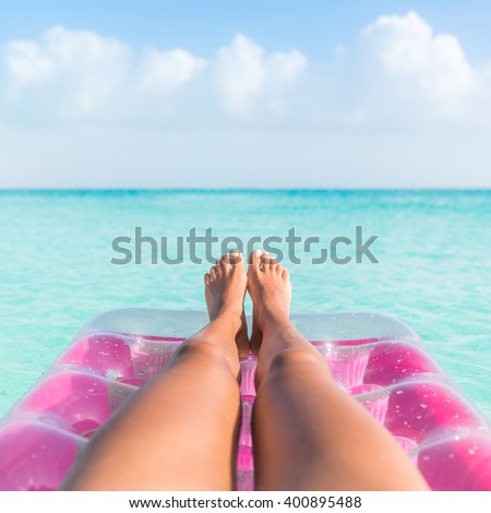 Summer vacation girl lower body closeup. Woman tanning legs  relaxing in ocean on pink inflatable swimming pool air mattress bed floating in turquoise water background. Suntan at tropical beach. - stock photo