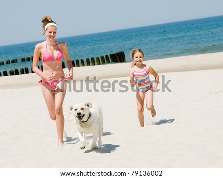 Summer vacation - girls with dog playing on the beach