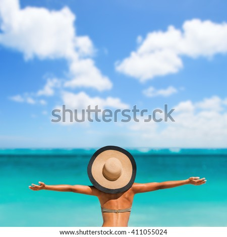 Summer vacation happiness carefree joyful sun hat woman with open arms in success enjoying tropical beach destination. Holiday bikini girl relaxing from behind on Caribbean vacation. Sky copyspace. - stock photo