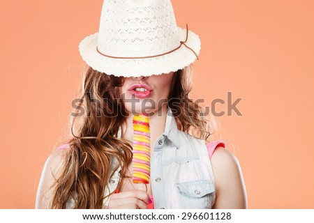 Summer vacation happiness concept. Funny cheerful woman covering eyes with straw hat eating popsicle ice cream orange background - stock photo