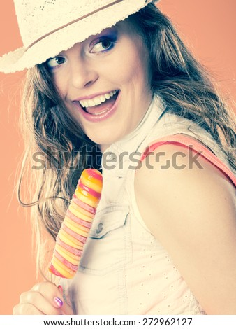 Summer vacation happiness concept. Smiling cheerful woman in straw hat eating popsicle ice cream orange background