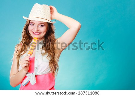 Summer vacation happiness concept. Smiling joyful and cheerful woman fashionable female model eating popsicle ice pop on blue background - stock photo