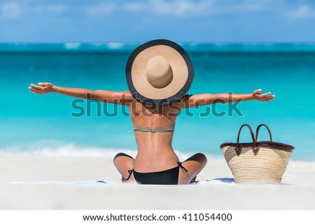 Summer vacation happy carefree joyful bikini woman arms outstretched in happiness enjoying tropical beach destination. Holiday girl sitting with sun hat relaxing from behind on Caribbean vacation. - stock photo