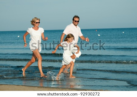 Summer vacation - happy family running in the sea - stock photo