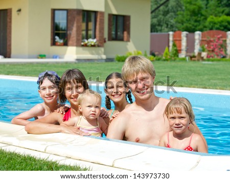 Summer vacation. Happy family with four kids in swimming pool outdoors