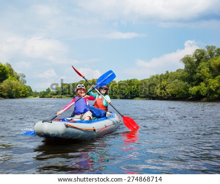 Summer vacation - Happy girl with her mother kayaking on river. - stock photo