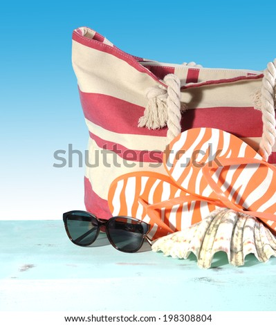 Summer vacation holiday gear with red and white strip beach bag, flip flop things, shell and sunglasses on a aqua blue table against a blue sunny sky.
