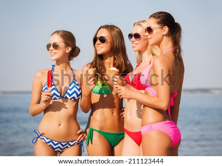 summer vacation, holidays, food, travel and people concept - group of smiling young women eating ice cream on beach