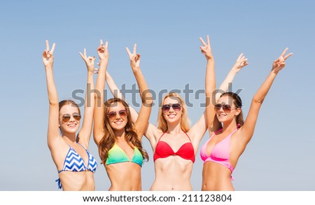 summer vacation, holidays, gesture, travel and people concept - group of smiling young women showing peace or victory sign over blue sky background - stock photo