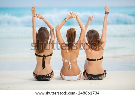 summer vacation, holidays, gesture, travel and people concept - group of young women sitting on beach from back. Beautiful Sexy Girls in Bikinis on Tropical Sunny Beach - stock photo