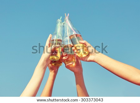 summer vacation, holidays, party and people concept - close up of many hands clinking bottles with lemonade or beer over blue sky background