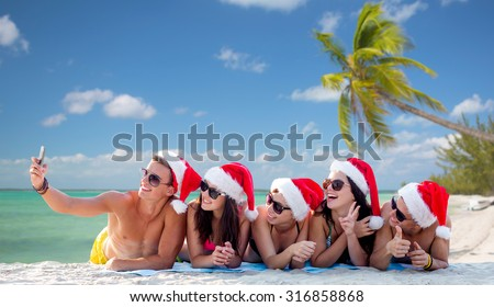 summer vacation, holidays, technology, travel and people concept - group of friends in santa helper hats taking selfie with smartphone on beach - stock photo