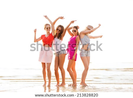 summer vacation, holidays, travel and people concept - group of smiling young women in sunglasses and casual clothes dancing on beach - stock photo