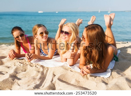 summer vacation, holidays, travel and people concept - group of smiling young women in sunglasses lying on beach - stock photo