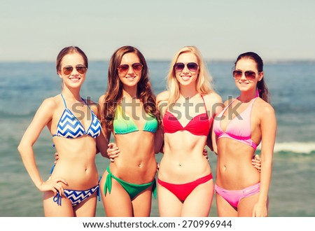 summer vacation, holidays, travel and people concept - group of smiling young women on beach - stock photo