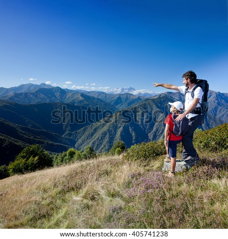 Summer vacation in mountain. Father and son standing in a mountain meadow. The man points to a direction, showing something to the boy. Summer season, clear blue sky. Piemonte, west italian Alps.