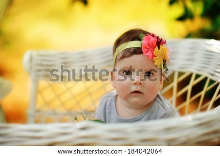 summer vacation in the garden sitting in a wicker chair cute little girl with a flower on her head