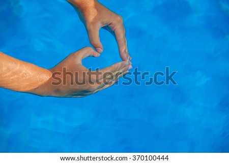 summer vacation love heart shaped hands in pool.  - stock photo