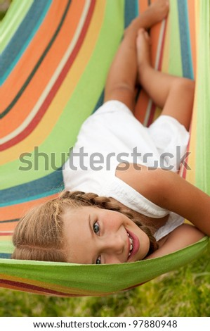 Summer vacation - lovely girl in colorful hammock - stock photo