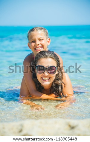 Summer vacation - Mother and cute daughter playing and swimming in the transparent sea - stock photo
