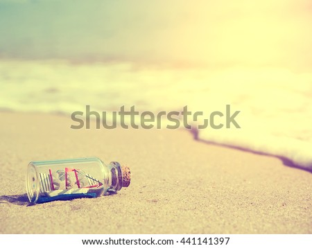 Summer vacation or traveling concept photo of a ship in the bottle lying on the beach with sea blur background and sunlight.  Vintage style photo and filtered process.
