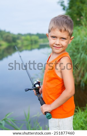 Summer vacation - Photo of little boy fishing on the river. - stock photo