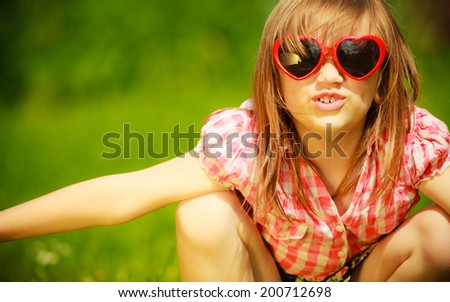 Summer vacation. Portrait of cute little girl kid child in red sunglasses in the shape of heart playing in flying outdoor.