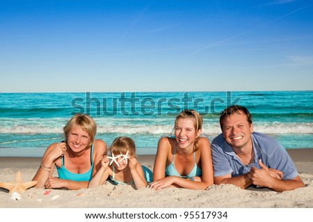 Summer vacation - portrait of happy family at the beach - stock photo