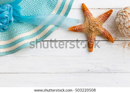 Summer vacation relaxation background theme with seashells, loose sand, hat, sunglasses and white wood background with copy space