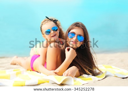 Summer vacation, relaxation, travel - mother and child lying resting on beach together - stock photo