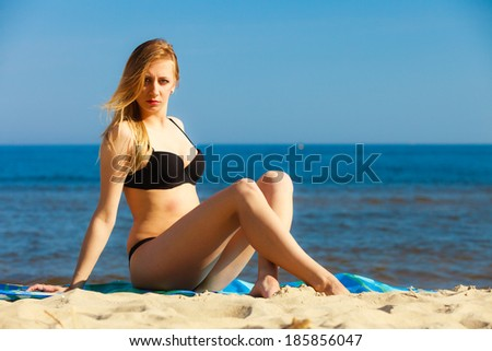 Summer vacation. Sexy girl in bikini sunbathing tanning on the beach. Young woman relaxing on the sea coast. Summertime.