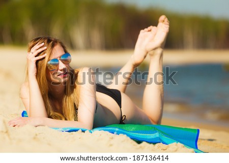 Summer vacation. Sexy girl in bikini sunbathing tanning on the beach. Young woman relaxing on the sea coast. Summertime. - stock photo