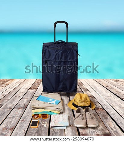 summer vacation, tourism and objects concept - travel bag, map, air ticket and clothes with personal stuff over wooden floor and sea background - stock photo
