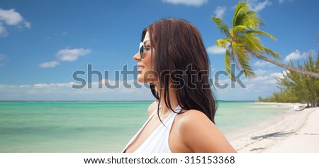 summer vacation, tourism, travel, holidays and people concept -face of smiling young woman in swimsuit with sunglassesover tropical beach background