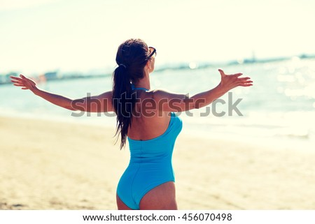 summer vacation, tourism, travel, holidays and people concept -young woman in swimsuit posing on beach from back - stock photo