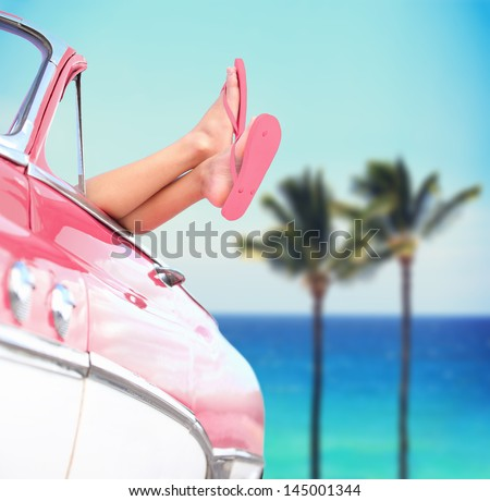 Summer vacation travel freedom concept with cool convertible vintage car and woman feet out of window against tropical sea background with palm trees. Girl relaxing enjoying vacation.