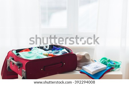 summer vacation, travel, tourism and objects concept - close up of travel bag with clothes and stuff - stock photo
