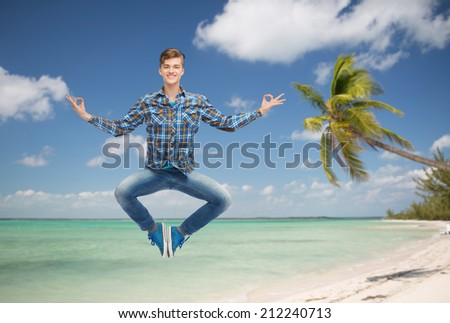 summer vacation, travel, tourism, freedom and people concept - smiling young man hanging of flying in air in pose of yoga over tropical beach background